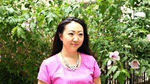Jennifer Pink Outfit Head Shot Flower Background Side Glance EDITED